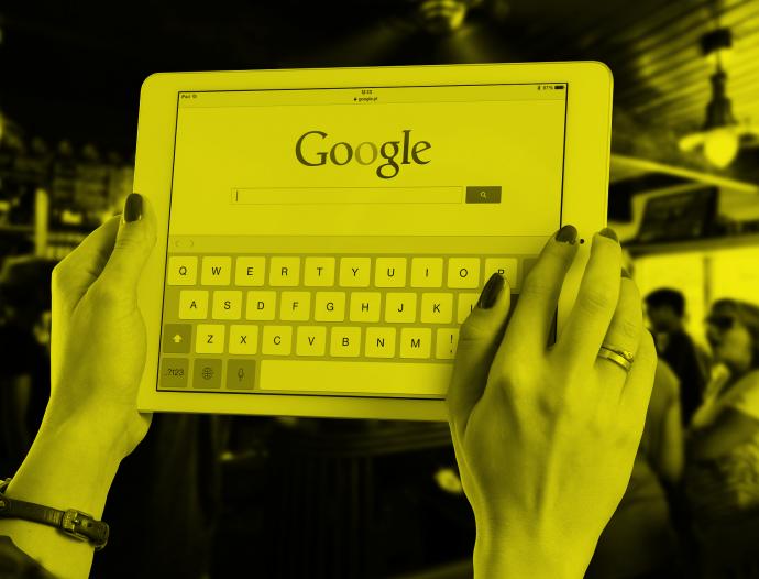 Mãos de mulher seguram um Iped em que aparece uma tela de pesquisa Google.