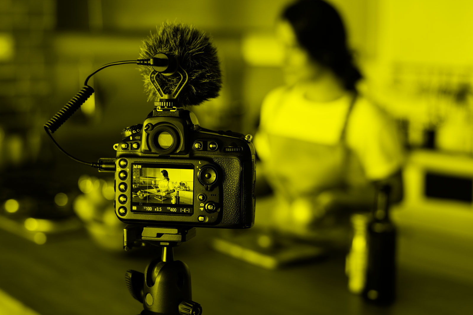 Câmera posicionada em um tripé filma uma mulher cozinhando.